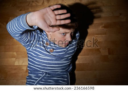 Child abuse composition of a frightened young boy sitting on the wooden floor in a light of a flashlight circle - stock photo