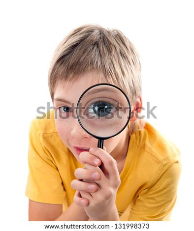 Child aged 10-12 years looking through a magnifying glass.