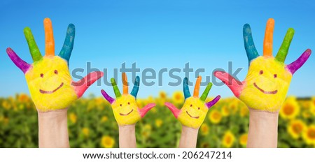 Child and adult smiling hands on summer background. Family fun concept. - stock photo