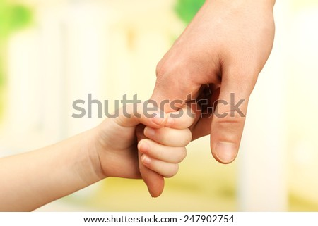 Child and father hands on bright background - stock photo