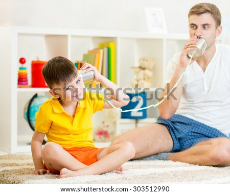 Child and father plays having a phone call with tin cans - stock photo