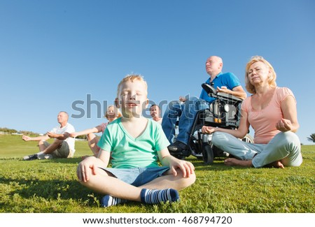 Child and Group of People with Disabled Man practicing yoga.