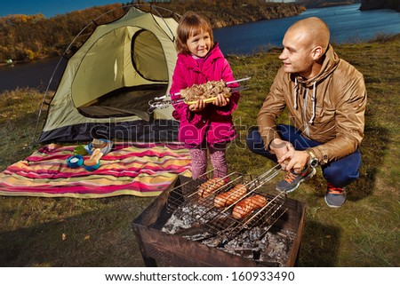 Child and her father are cooking grilled shish kebab outdoor - stock photo