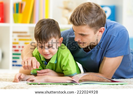 child and his father read a book on floor at home - stock photo