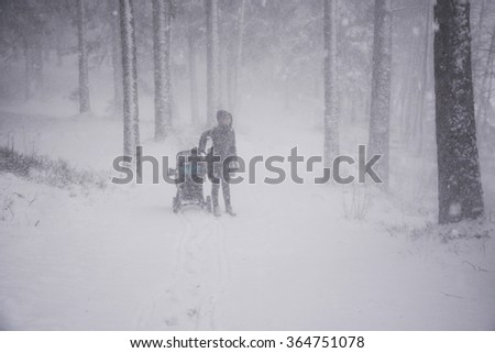Child and mother at winter forest at strongest snowstorm - stock photo