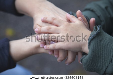 Child and mother holding hands in unity and supporting each other. - stock photo