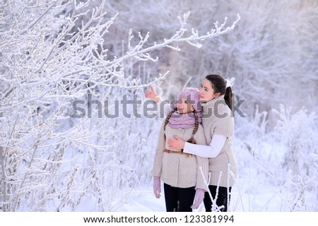 Child and parent in nature. Lots of snow and frost. White tree branches. People look at the frost. - stock photo