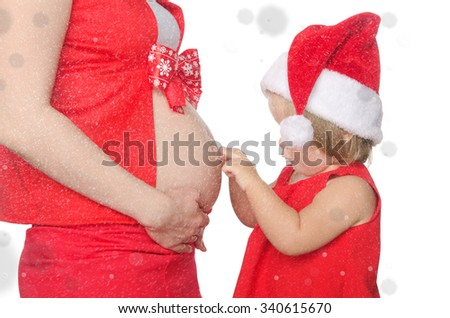 child and pregnant woman belly at Christmas and snowflakes - stock photo