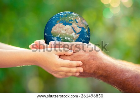 Child and senior holding planet in hands against green spring background. Earth day holiday concept. Elements of this image furnished by NASA - stock photo