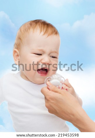 child and toddle concept - crying baby with dummy - stock photo