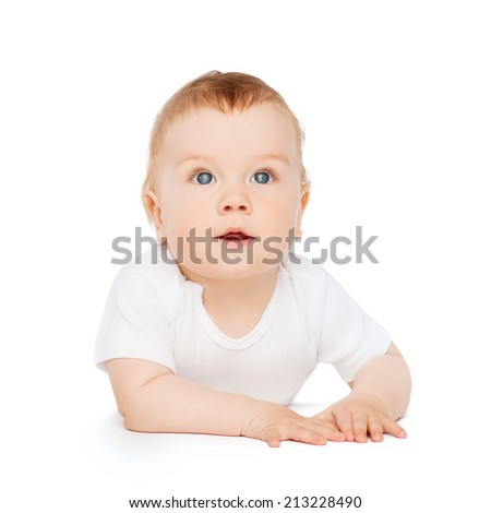 child and toddler concept - curious baby lying on floor and looking up