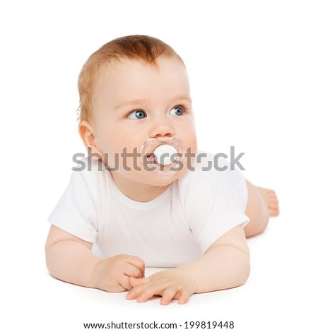child and toddler concept - smiling baby lying on floor with dummy in mouth - stock photo