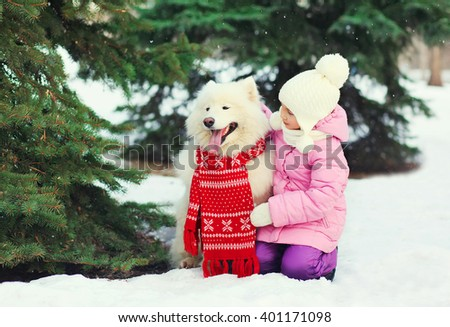 Child and white Samoyed dog in red scarf near christmas tree in winter day - stock photo