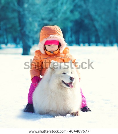 Child and white Samoyed dog lying on snow in winter day