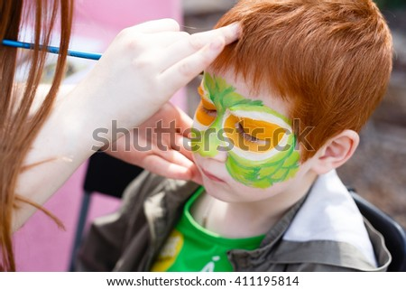 Child animator, artist's hand draws face painting to redhead child. Redhead boy with funny face painting. Painter makes reptile eyes at him. Children holiday, event, bithday party, entertainment. - stock photo