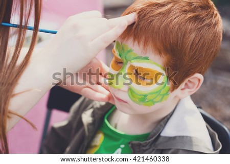 Child animator, artist's hand draws face painting to redhead child. Redhead boy with funny face painting. Painter makes reptile eyes at him. Children holiday, event, birthday party, entertainment. - stock photo