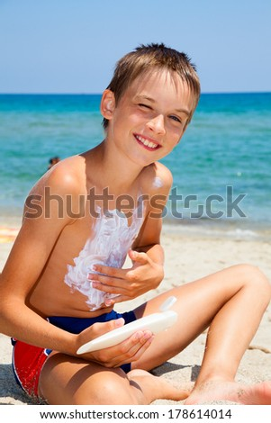 Child apply too much of sunblock cream - stock photo