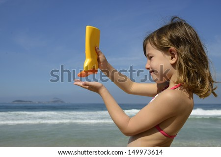Child applying sunscreen lotion on the beach - stock photo