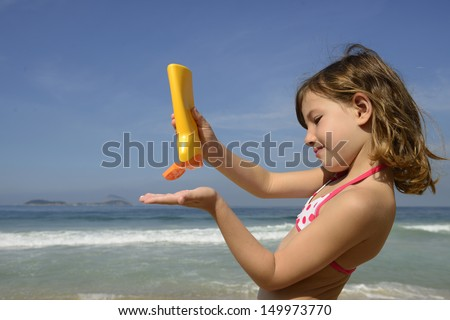 child applying sunscreen on the beach during summer vacation - stock photo