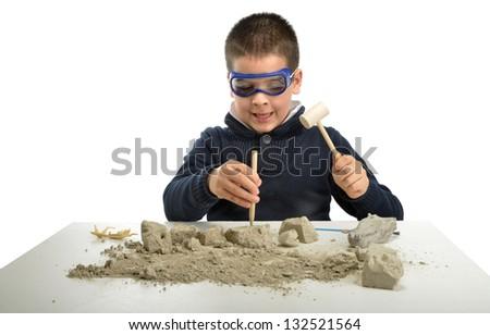 Child archaeologist excavating dinosaur skeleton isolated on white background - stock photo