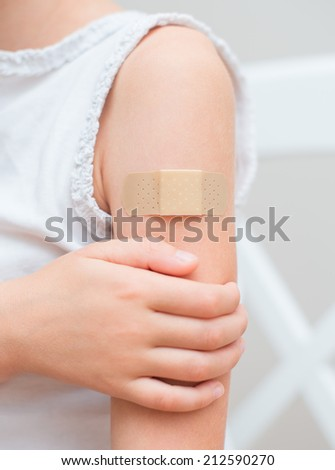 Child arm with an adhesive bandage. - stock photo
