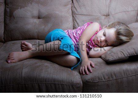 Child asleep late at night on the couch. - stock photo