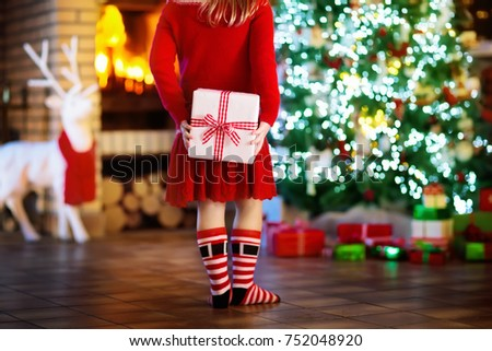 Child at Christmas tree and fireplace on Xmas eve. Little girl holding present box. Child with gift. Family with kids celebrating Christmas at home. Gifts for winter holidays at fire place. Back view.