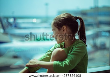 Child at the airport near the window looking at airplanes and waiting for time of flight - stock photo