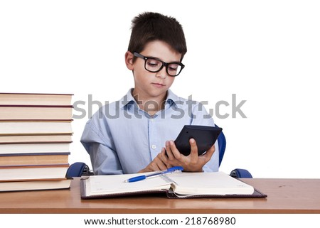 child at the table with books from school