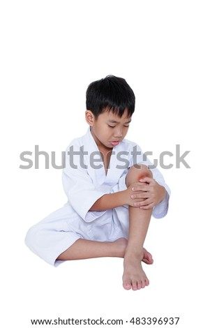 Child athletes taekwondo Injured. Asian handsome boy looking at wound on his knee, isolated on white background. Sad boy sitting at studio. Concept of sport physical accident and sport injury.