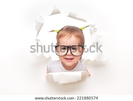 child baby girl with funny tails with glasses peeping through a hole in an empty white paper poster - stock photo