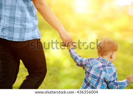 Child, baby holding an adult's hand. Father and son on a walk. The kid and the man. - stock photo