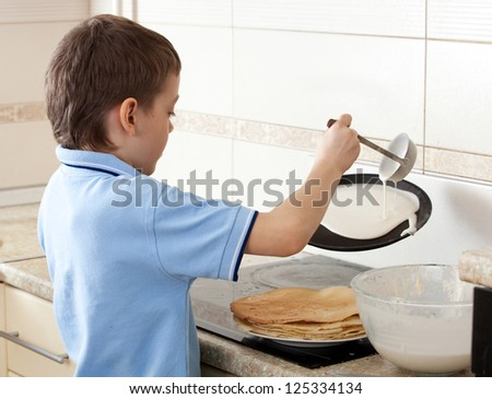 Child bakes pancakes in the kitchen. Boy cooking breakfast - stock photo