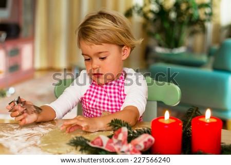 child baking cookies for christmas. cookies for the christmas season - stock photo