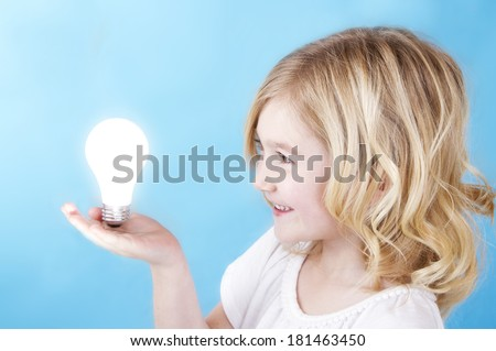 Child balancing a glowing light bulb on her hand with a blue background.