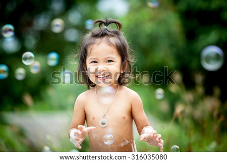 Child bathing outdoor,asian little girl having fun to play with water,foam and bubble in outdoor on green bokeh background,selective focus - stock photo