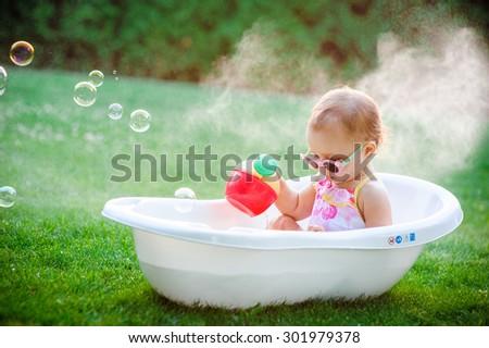 child bathing  with foam bath. - stock photo