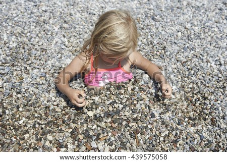Child blond Girl covered in beach pebbles, smiling and enjoying free time on the beach. Family and children on vacation, summer fun concept. - stock photo