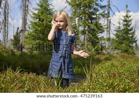 Child blond little girl picking fresh berries on blueberry field in forest.