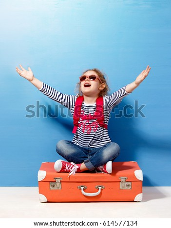 Child blonde girl with pink vintage suitcase ready for summer vacation. Travel and adventure concept