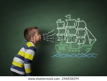 Child blowing a chalk drawing of a sailboat on a blackboard concept for wishing, dreams, hope and aspirations - stock photo