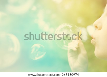 Child blowing bubbles.  Instagram effect - stock photo