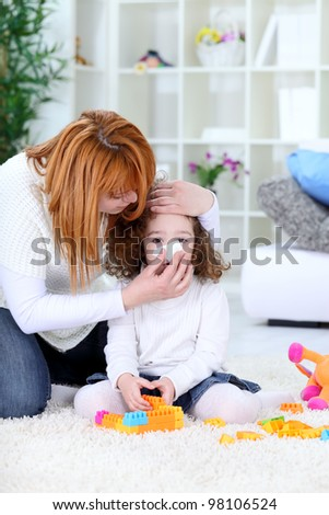 Child blowing nose, mothers help with handkerchief - stock photo