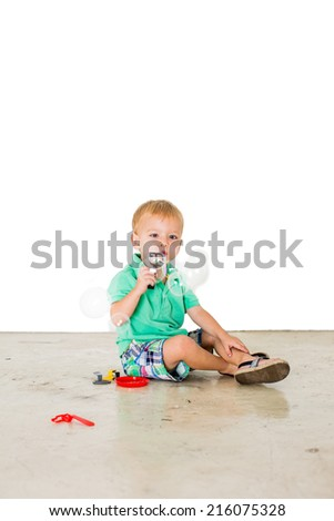 Child blowing soap bubbles in white background