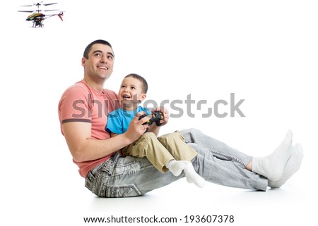 Child boy and dad playing with RC helicopter toy - stock photo