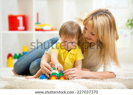child boy and woman play with toy indoor - stock photo
