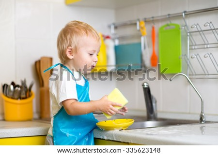 Child boy cleaning the kitchen after dinner - stock photo