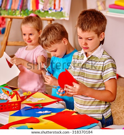 Child boy cutting out scissors paper heart - stock photo