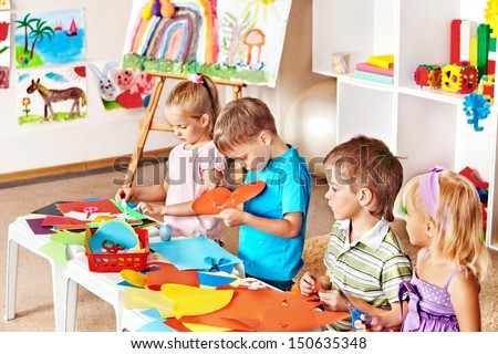 Child boy cutting out scissors paper in preschool. - stock photo