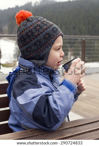 Child boy drinking a hot drink from a flask cup in winter  .